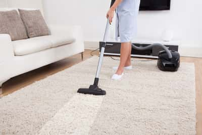 Photo of maid vacuuming a grey colored rug in living room