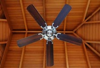 Photo looking up at a dark ceiling fan on a light brown vaulted ceiling