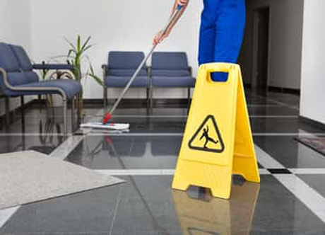 Man mopping an office floor with a yellow do not slip sign open.