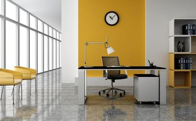 Small office with single desk and chair with white and yellow walls.