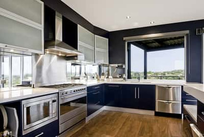 Spotless modern kitchen with black cabinets, stainless steel appliance, and a fantastic country view out the window.
