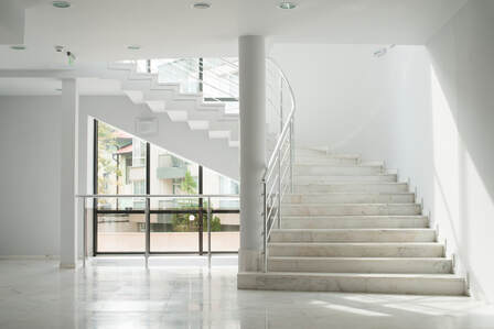 Marble floor leading to bay window with curved grey stair wrapping above the window